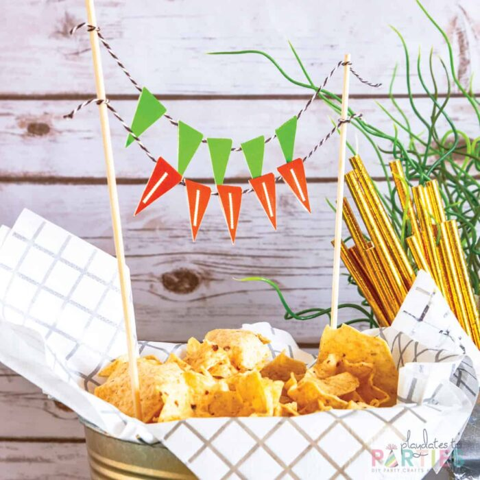 close up of chips in a bucket with mini printable bunting that looks like football laces
