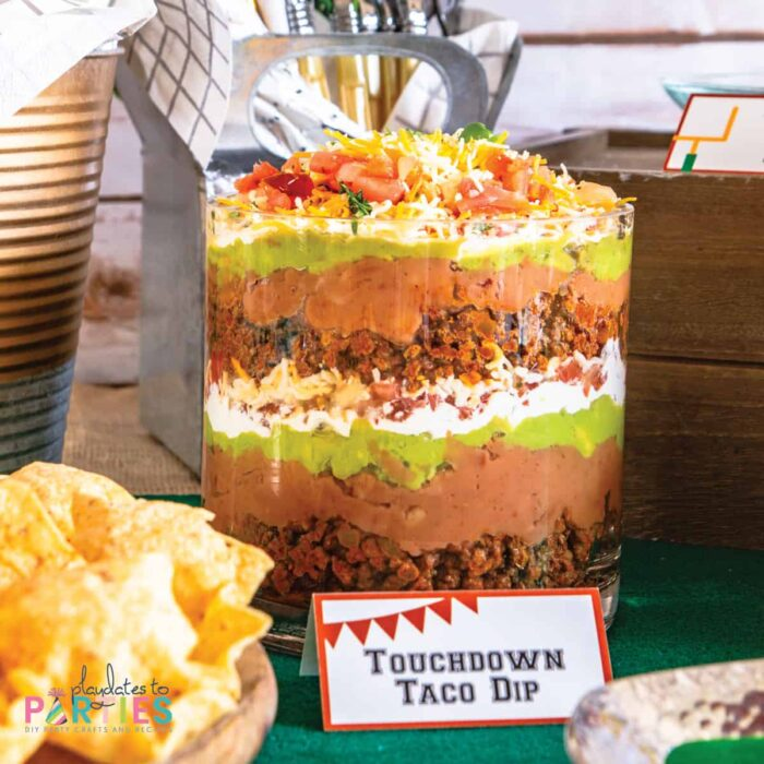 layered dip in a glass bowl with a printable party label that says touchdown taco dip