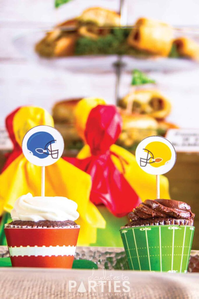 close up of two cupcakes. one has a printable topper with a blue football helmet the other has a printable topper with a yellow football helmet