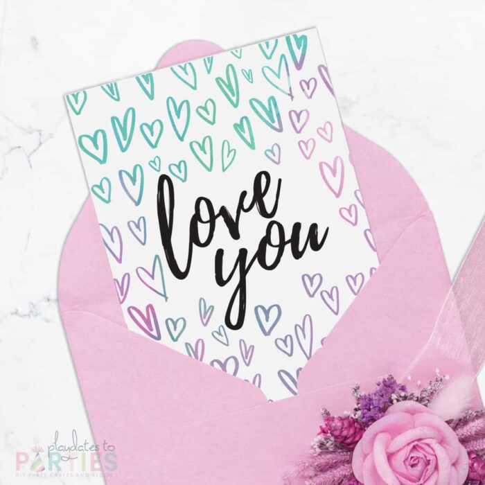 Picture of a 5x7 card peeking out of a pink envelope. The card has watercolor hearts surrounding the words love you in black script