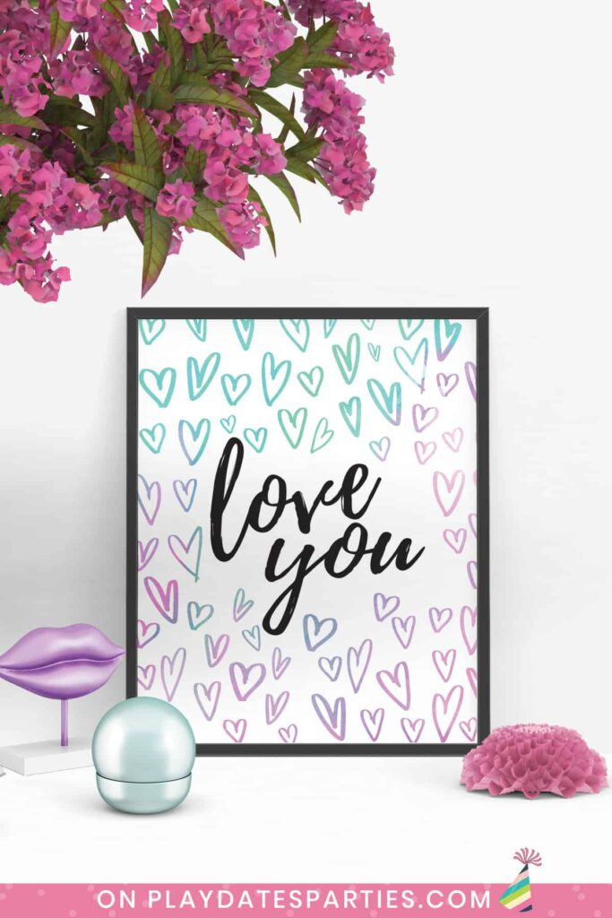 framed print of the words love you in black script surrounded by hearts in watercolors ranging from pink to purple to aqua.