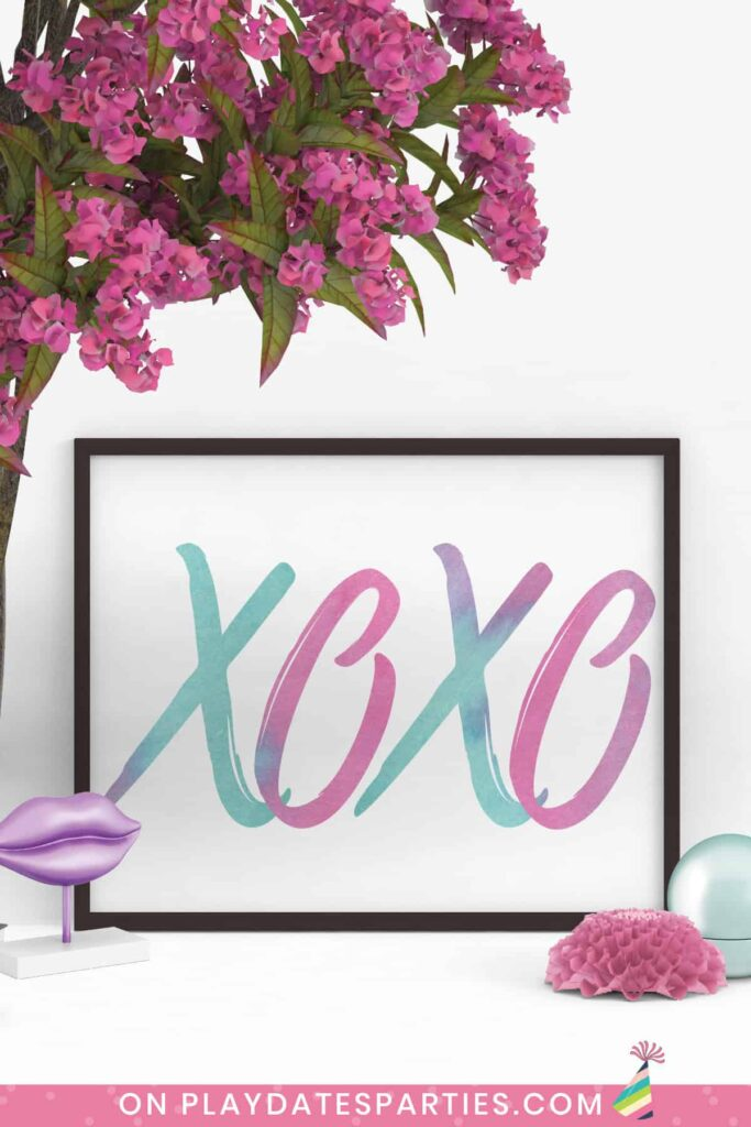 framed landscape print with a black frame. The print has large letters XOXO in watercolor script