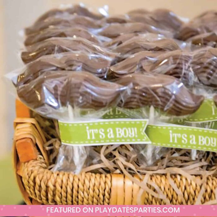 mustache lollipop favors in a basket with a green tag that says It's a Boy
