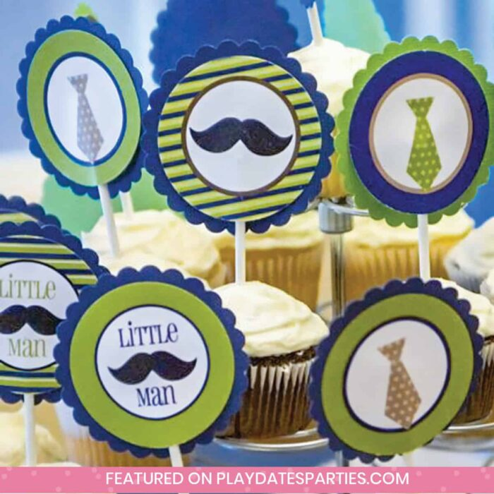 close up of green and blue party cupcake toppers with mustaches and neckties that say little man