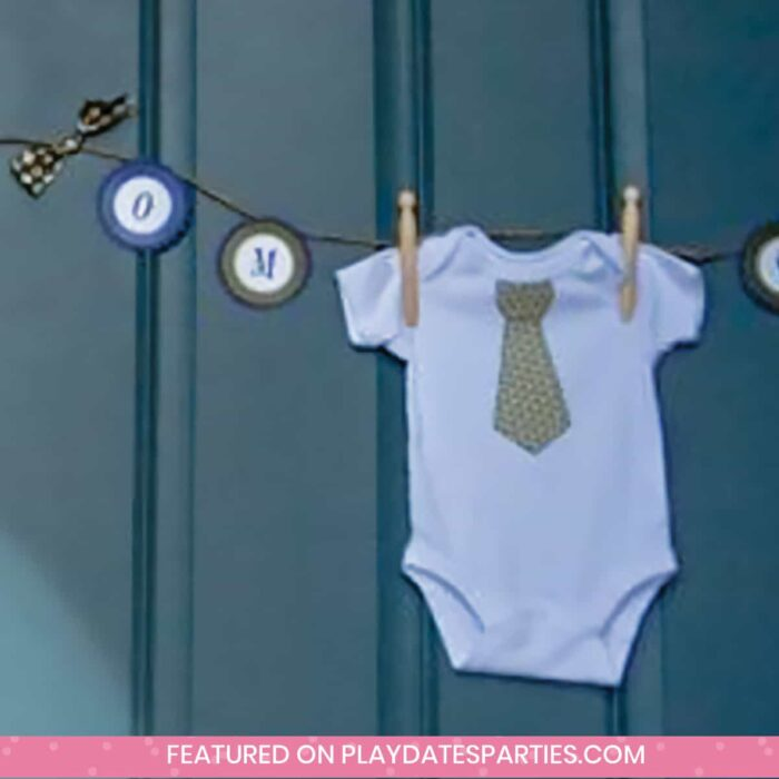 baby onesie with a necktie hanging as decoration on a party banner