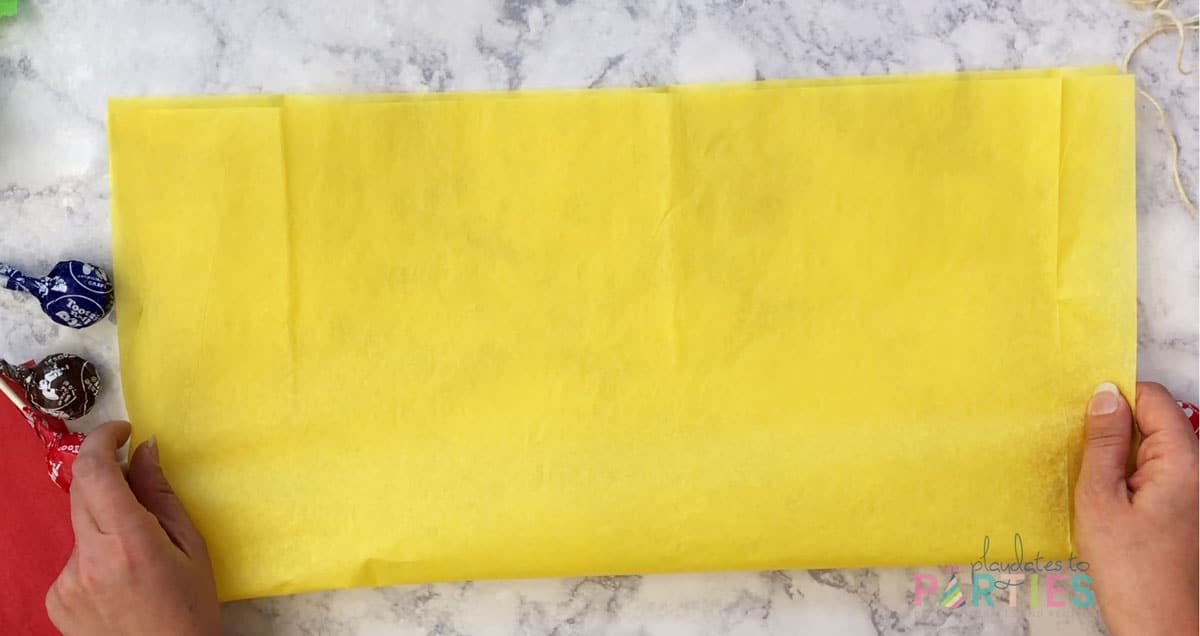 top view of folding a piece of yellow tissue paper in half lengthwise