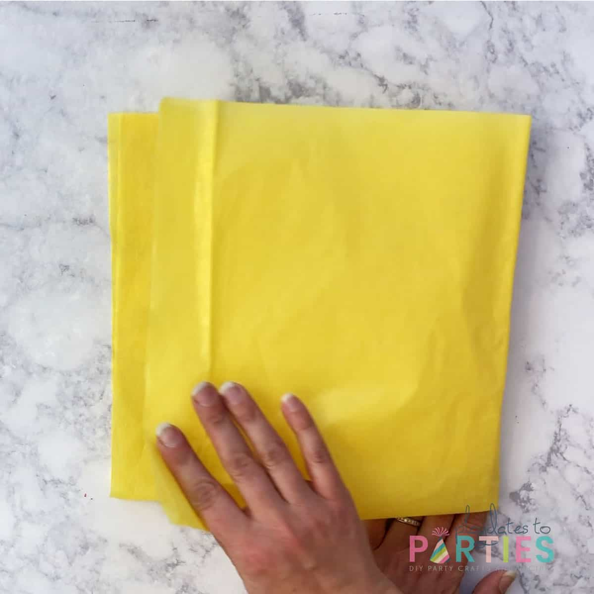 overhead view of folding yellow tissue paper a second time along the short side to create a square