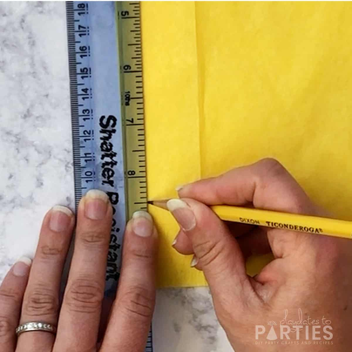 step 2 - measuring and marking 8 and one half inches from the top of the folded tissue paper