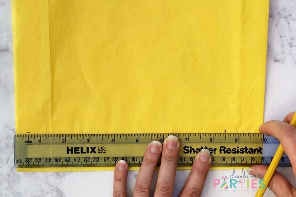step 3 - measuring and marking 8 and one half inches across the folded tissue paper