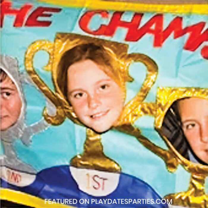 kids with faces in a photo prop that looks like trophies with words the champs across the top
