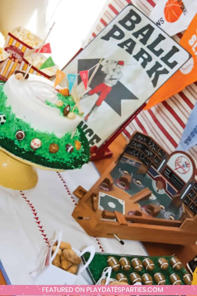 angled photo of a party table with a cake, wooden baseball themed game board, and snacks