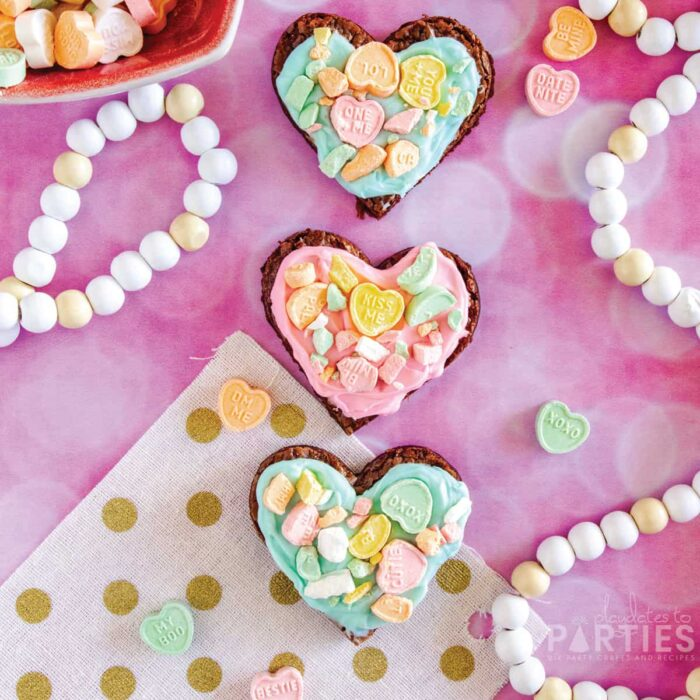 Three Valentine's Day brownies on a pink surface surrounded by party decorations and conversation hearts