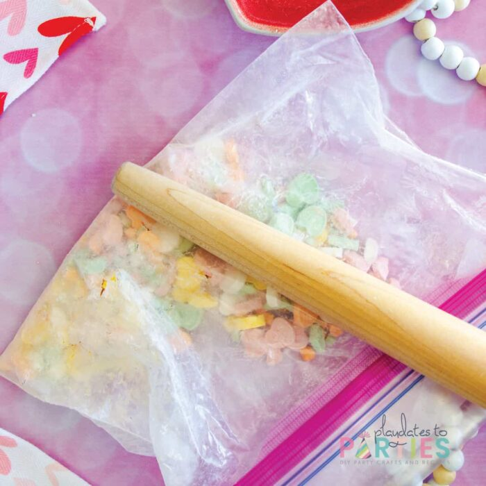 crushing conversation hearts in a zip top bag with a rolling pin