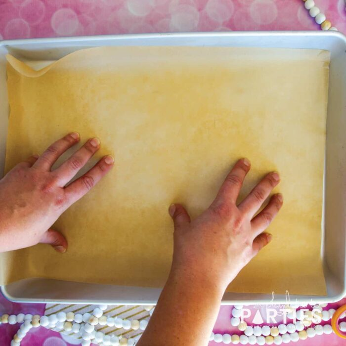 placing a sheet of parchment paper in the bottom of a baking pan