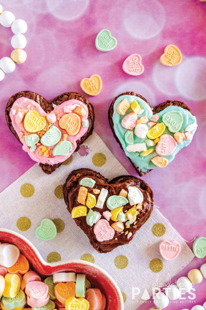 Three heart shaped brownies on a pink surface with pink, blue, and chocolate frosting and crushed conversation hearts on top.