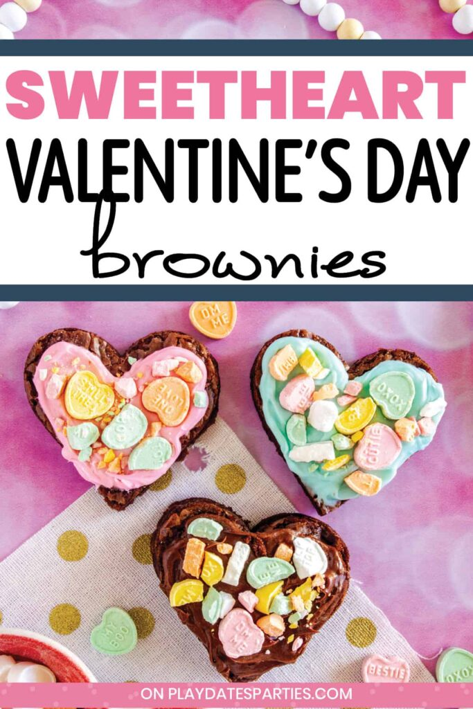 three heart shaped brownies on a pink surface surrounded by conversation hearts with the text Sweetheart Valentine's Day brownies