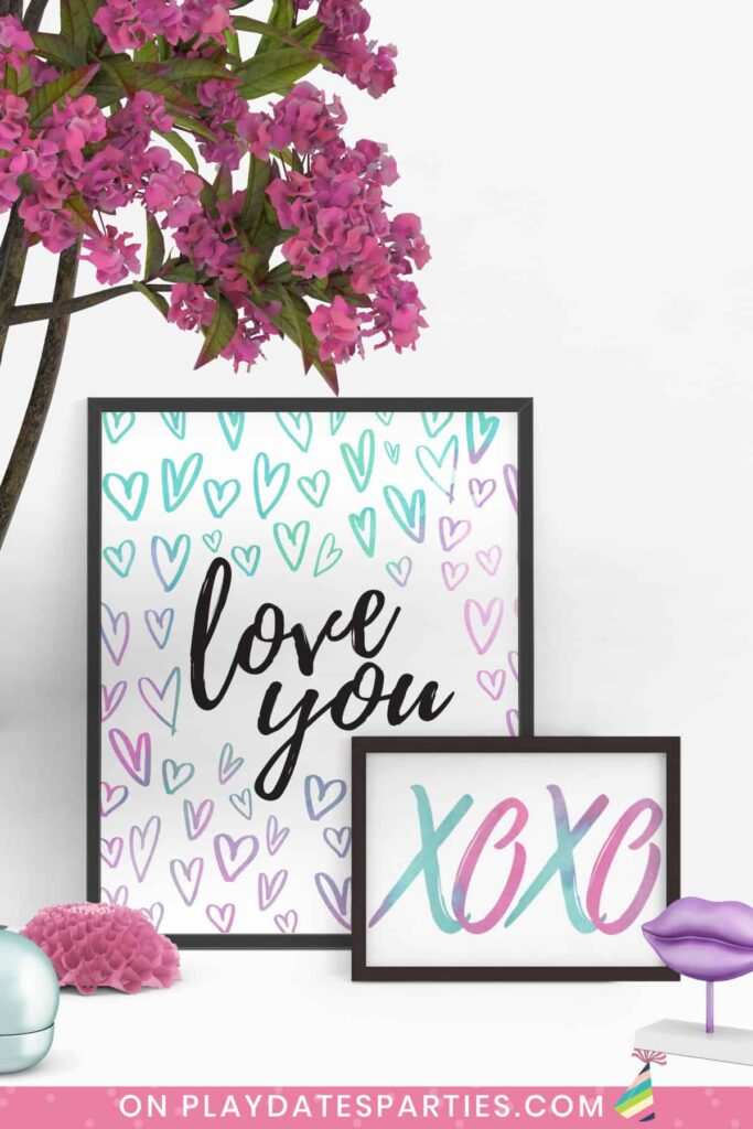two watercolor Valentine's Day art prints on a white table in black frames