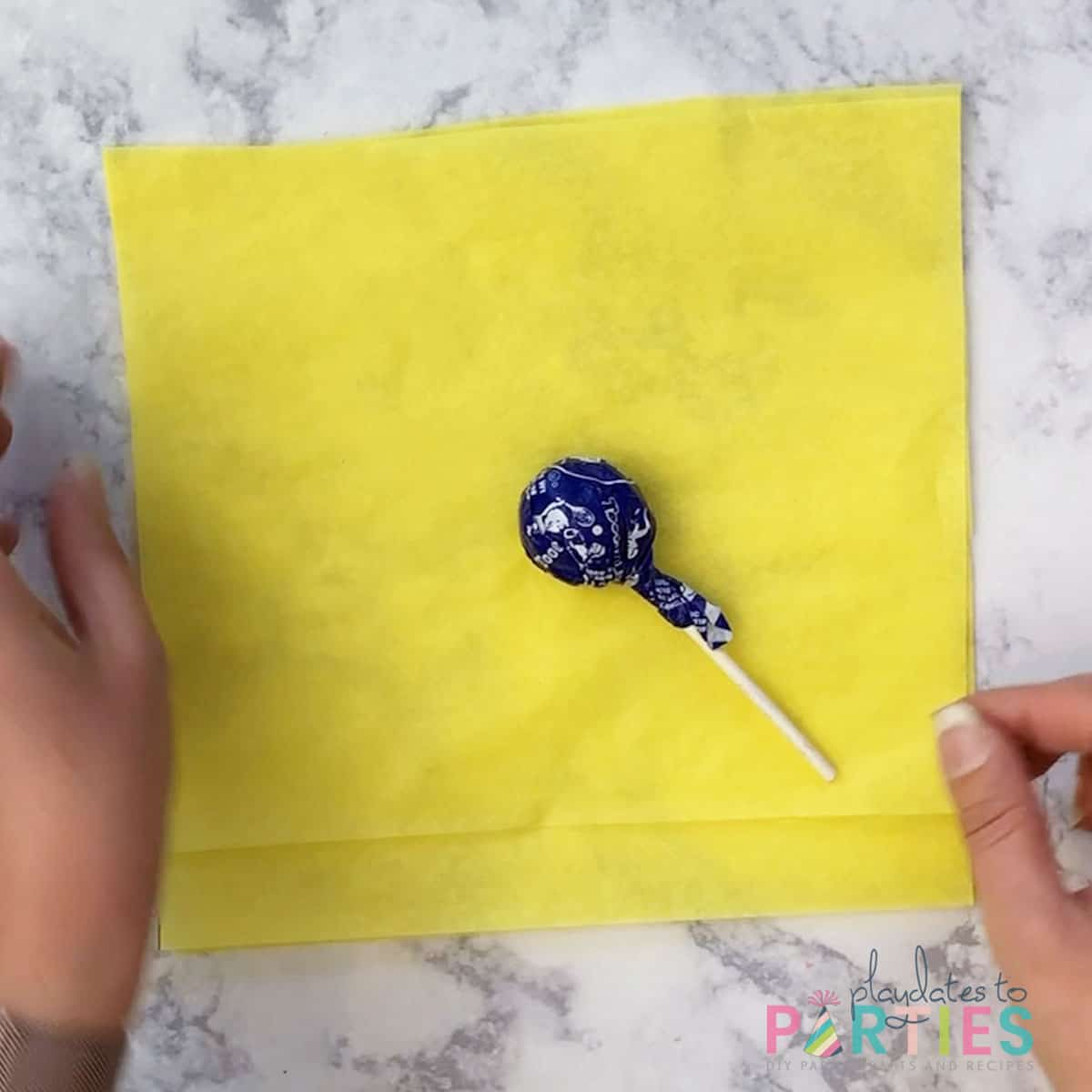 tootsie roll pop laying in the middle of square yellow tissue paper on a marble surface