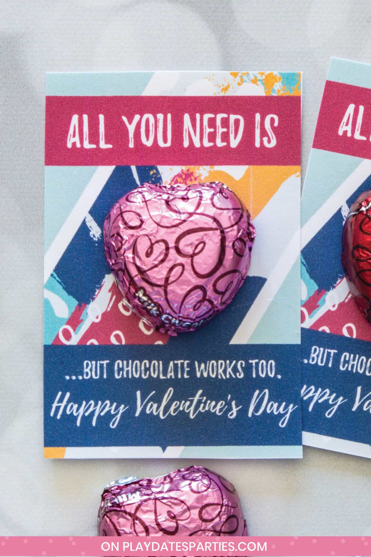 finished all you need is love chocolate valentine card with a pink chocolate heart on a gray surface