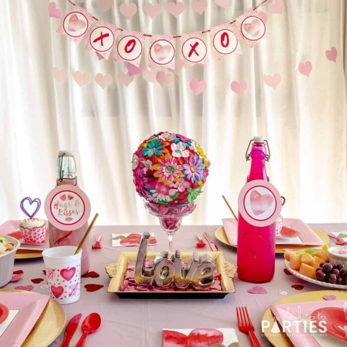 dining table decorated for Valentine's Day lunch with disposable plates and a centerpiece made with a margarita glass and a flower-covered pom