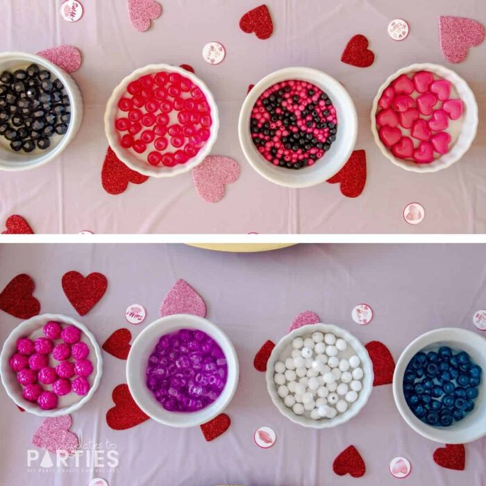 Overhead view of ramekins filled with beads on a pink table surrounded by glittery hearts and small party circles.