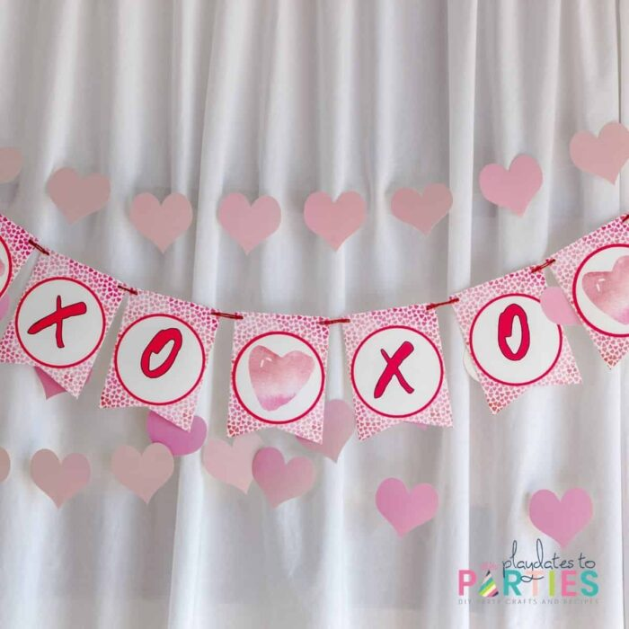 close up of a pink party banner with the letters XOXO in front of a white fabric backdrop and a garland made out of paper hearts.