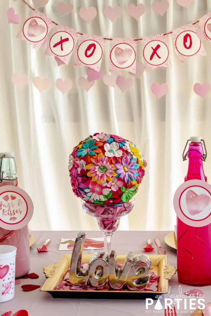 dining table set up for Valentine's Day with a centerpiece that says love, pink drink bottles, and a banner in the background that says XOXO
