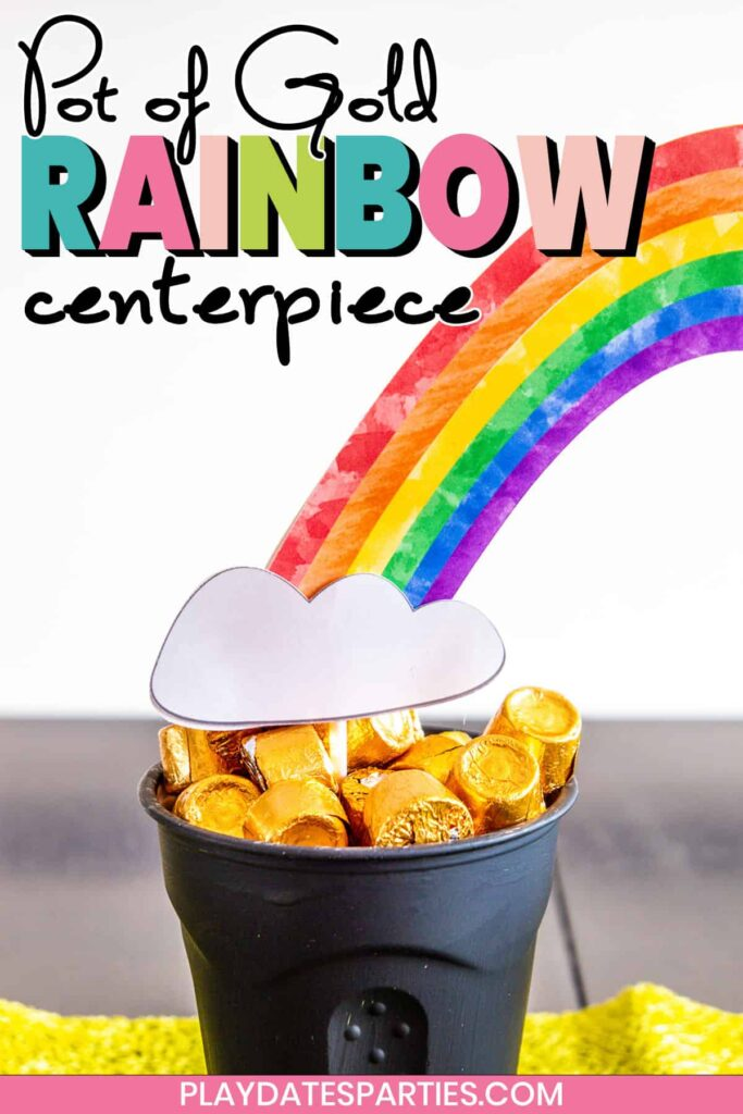 close up of a cup full of Rolos with a paper craft rainbow coming out of it with text overlay pot of gold rainbow centerpiece