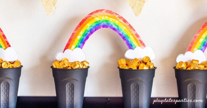 Three pot of gold rainbow decorations lines up on a shelf