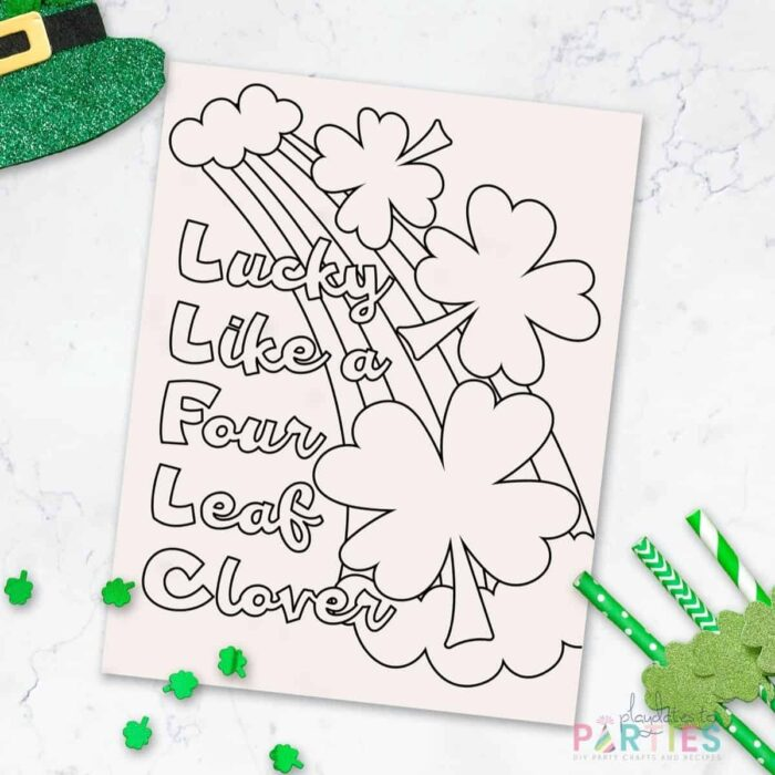 coloring sheet with a rainbow and four leaf clovers that says Lucky like a four leaf clover on a marble table with green decorations around it.