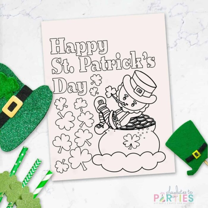 coloring sheet with a leprechaun that says Happy St. Patrick's Day on a marble table with St. Patrick's day decorations around it.