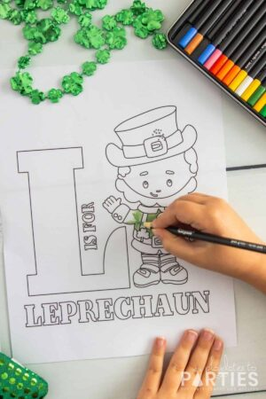 overhead image of a child coloring a sheet with a picture of a Leprechaun that says L is for Leprechaun