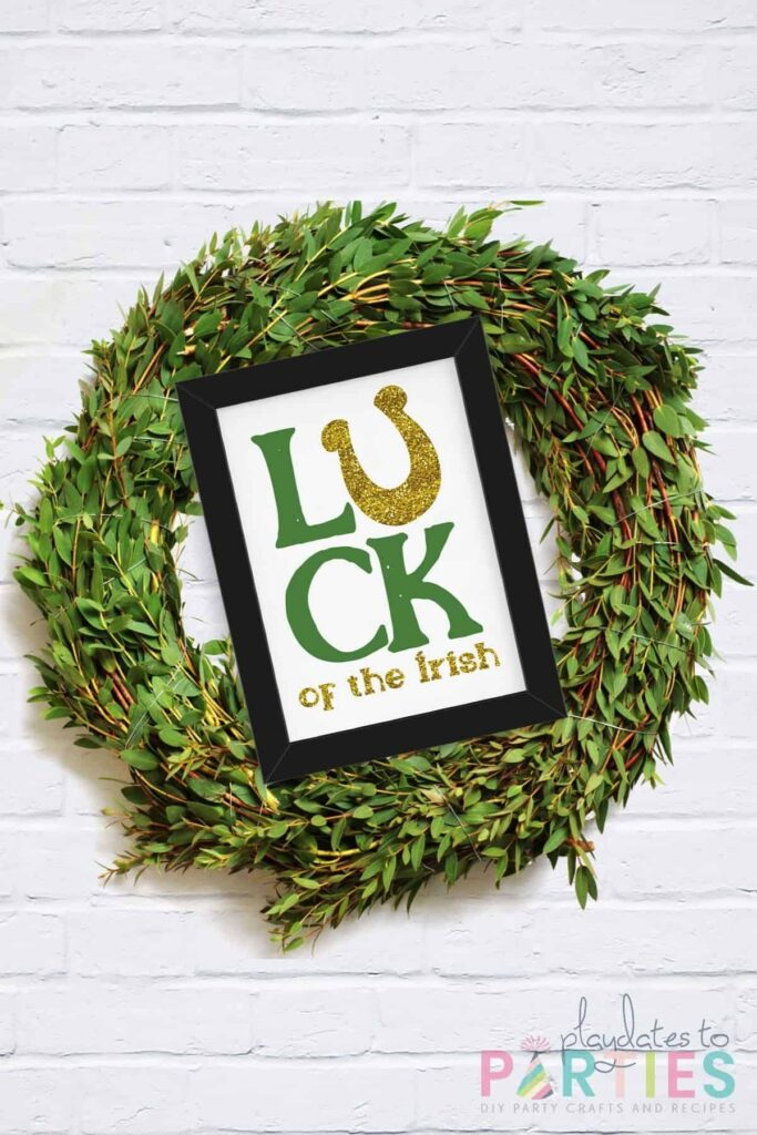 wreath on a white brick wall with a sign that says Luck of the Irish attached to the front.