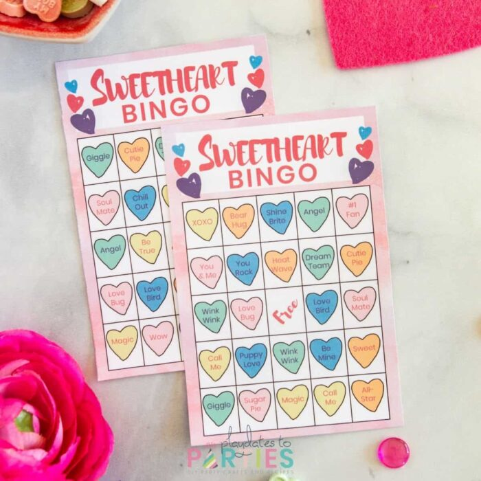 two Sweetheart bingo cards on a marble table surrounded by candy, flowers, and decorative hearts
