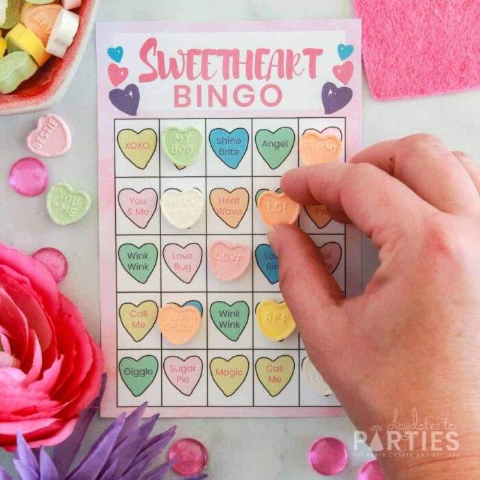 woman's hand placing a conversation heart candy on a bingo card for Valentine's Day
