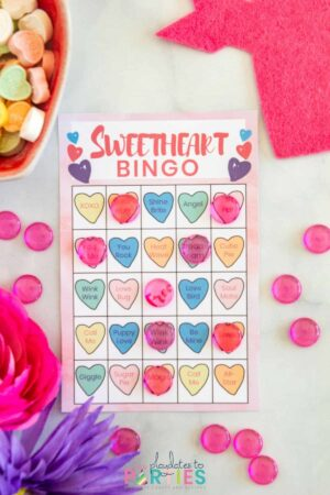 a pink bingo card with pictures of hearts and translucent pink acrylic confetti used as markers