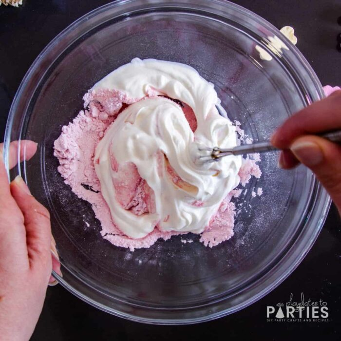 mixing pink powdered candy with sour cream