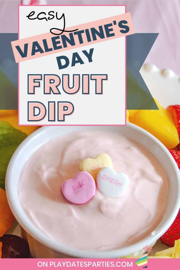 ramekin filled with pink dip and garnished with conversation hearts on a plate with fresh cut fruit. Text overlay reads easy Valentine's Day fruit dip.