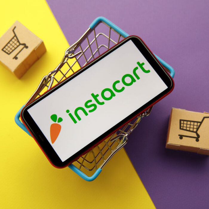 mini shopping basket with a phone on top and the Instacart logo.