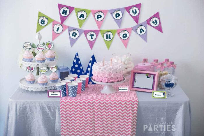 blue and pink party table with multicolored party printables that have a balloons and banners motif