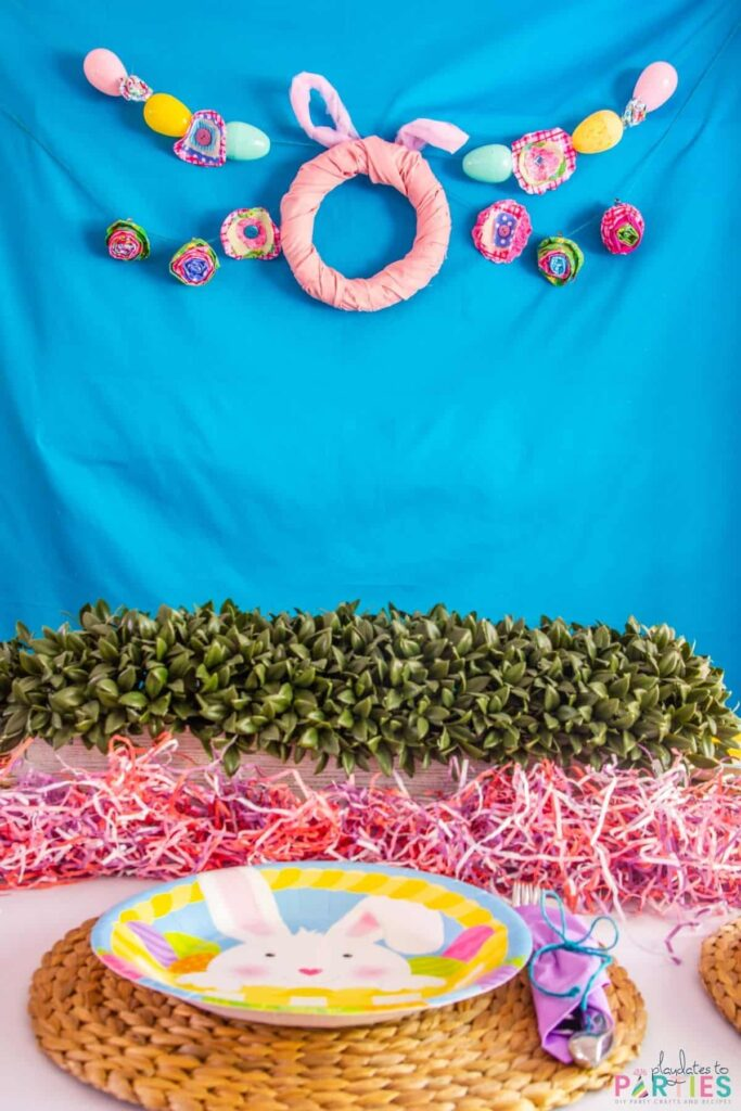 View of an Easter place setting and a bright blue backdrop with a bunny wreath and Easter egg garland