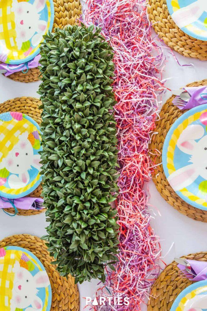 Overhead view of a dining table decorated for Easter with greenery and paper Easter grass
