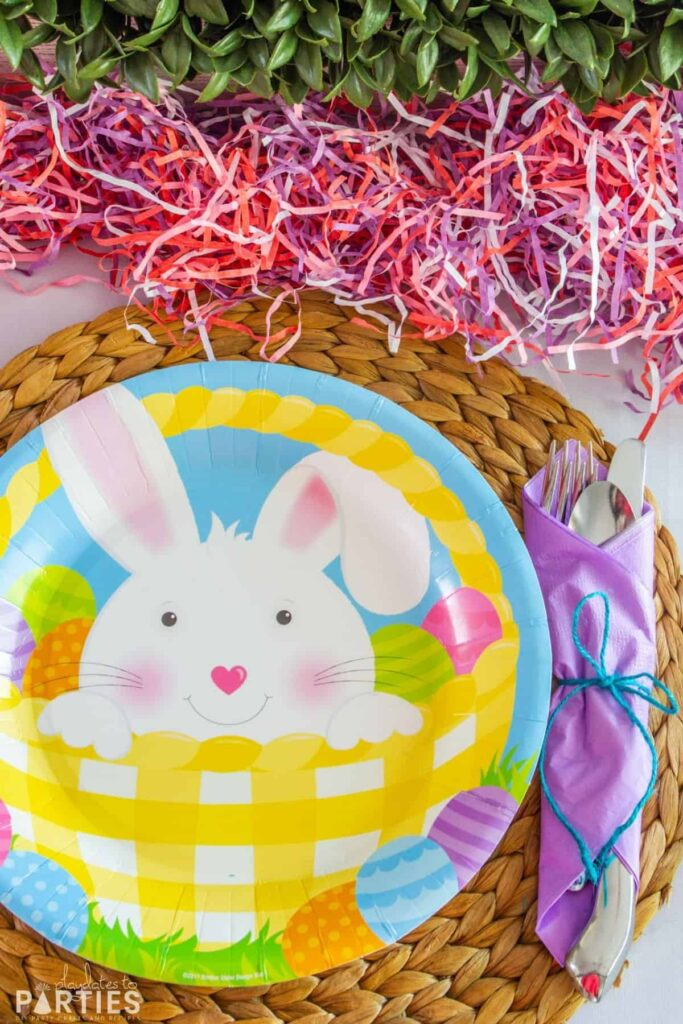 close up of an Easter plate on a woven placemat with utensils wrapped in a purple paper napkin