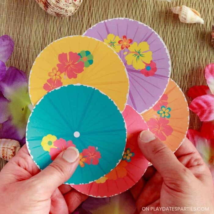 woman's hands holding 5 fruit cup labels in different colors that are fanned out