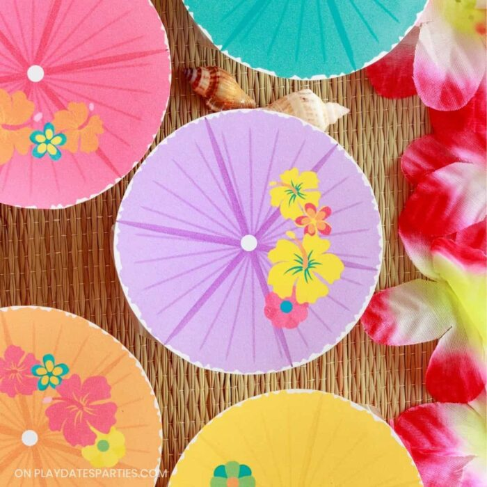 overhead view of fruit cups with printable labels on a grass beach mat with a pink lei nearby