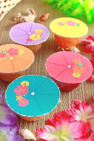 side view of fruit cups with labels that look like tropical drink umbrellas in a variety of luau colors