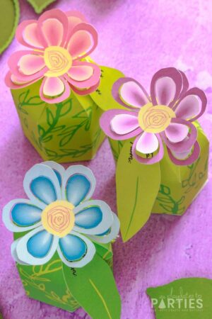 DIY flower favor boxes on a purple surface with flowers in pink, purple, and blue
