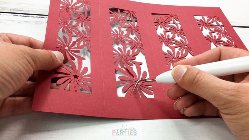 close up of using a weeding tool to pop small pieces out of a delicately cut cardstock design
