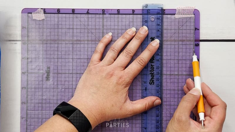 overhead image of a woman's hands measuring wax paper two inches from the edge of the sheet