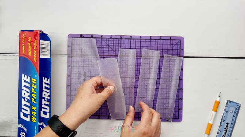 overhead image of a woman's hands collecting four wax paper sheets cut into 2 inch by 6.5 inch rectangles